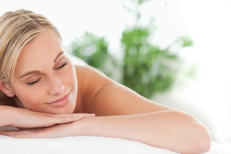 Close up of a woman lying on a lounger eyes closed in a wellness center photo