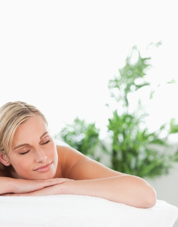 Close up of a blonde smiling woman lying on a lounger with closed eyes in a wellness center photo