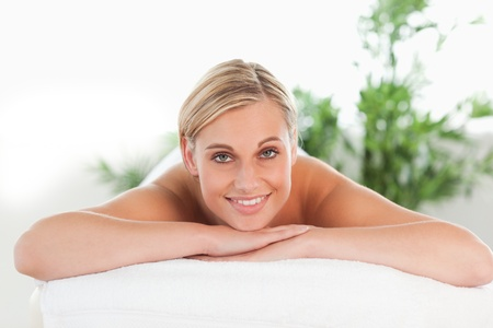 Close up of a blonde smiling woman relaxing on a lounger in a wellness center photo