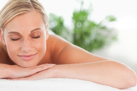 Close up of a blonde smiling woman relaxing on a lounger with eyes closed in a wellness center photo