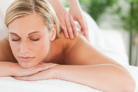 relaxation massage: Close up of a smiling woman relaxing with eyes closed on a lounger during a massage in a wellness center Stock Photo
