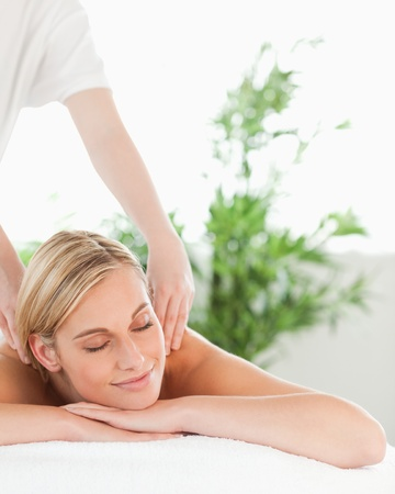 Close up of a blonde woman relaxing on a lounger enjoys a massage in a wellness center photo