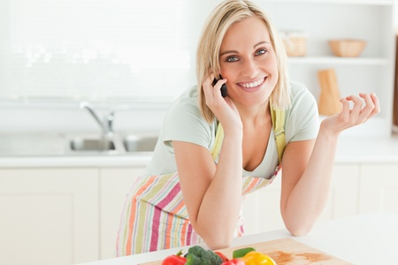 Close up of a gorgeous woman on phone looking into camera in the kitchen photo