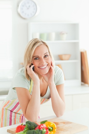 Gorgeous woman on phone looking into camera in the kitchen photo