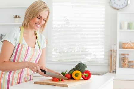 Cute woman cutting red pepper in kitchen photo