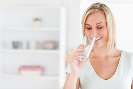 Gorgeous woman drinking water in her kitchen photo