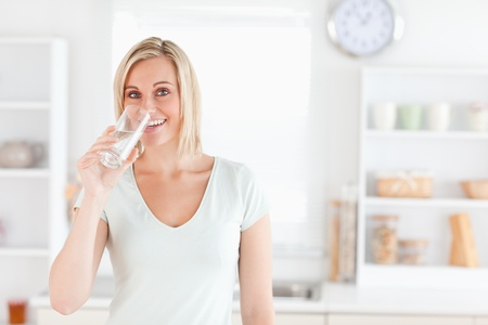 Charming woman drinking water while standing looks into camera in the kitchen photo