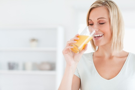 Smiling woman drinking orange juice in the kitchen Stock Photo - 11233027