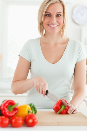 Woman cutting peppers looks into camera in the kitchen photo