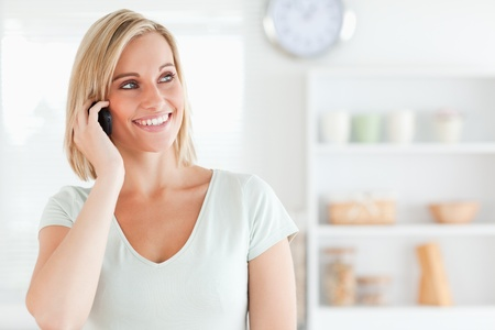 Close up of a young woman on phone in kitchen photo