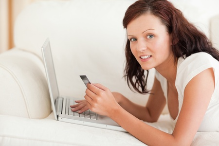 Dark-haired woman doing some online shopping looking into the camera in the livingroom photo