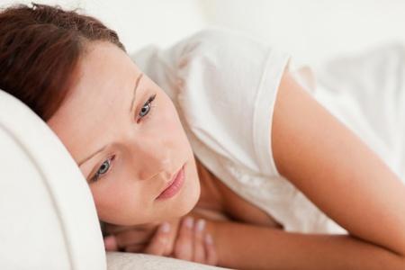 cara triste: Mujer triste acostado en una cama en un dormitorio