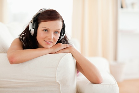 Dark-haired young woman listening to music relaxing in the livingroom photo