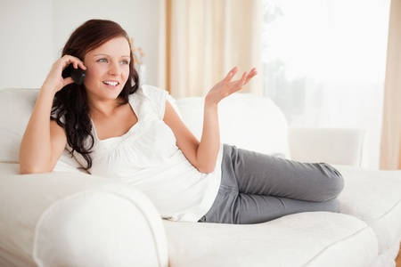 Red-haired woman relaxing on a sofa phoning in the livingroom photo