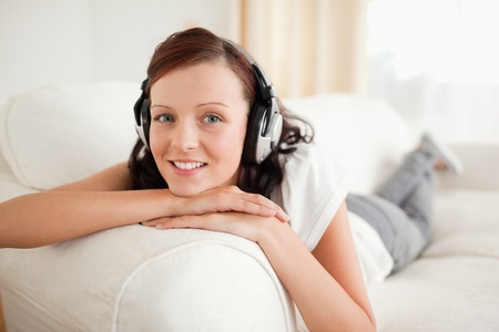 Relaxed red-haired woman with headphones looking into the camera in the livingroom photo