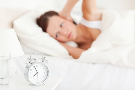 wanting: Good looking red-haired woman lying in bed not wanting to hear the alarm clock