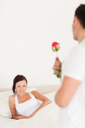 Young woman looking into camera when husband arrives with rose in her bedroom Reklamní fotografie