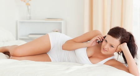 Woman sitting on a sofa while texting in the bedroom photo