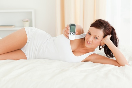 Woman showing a mobile in her bedroom photo