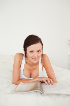 Close up of a Woman with a magazine looking into the camera in her bedroom photo