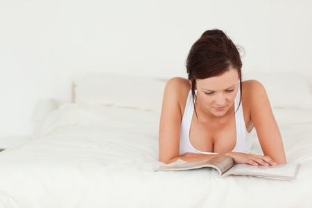 Portrait of a woman reading a magazine in her bedroom photo
