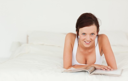 untroubled: Portrait of a woman reading a magazine looking into the camera in the bedroom Stock Photo