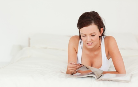 Cute woman reading a magazine in her bedroom photo