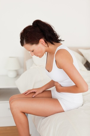 아픈: 아픈 느낌이 여자가 그녀의 침실에서 그녀의 침대에 앉아 스톡 사진