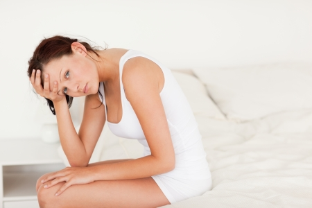Ill-feeling woman sitting on her bed in her bedroom Stock Photo - 11232524
