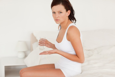 Ill woman taking pills in her bedroom photo