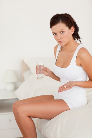 Sick woman showing pills in the bedroom photo