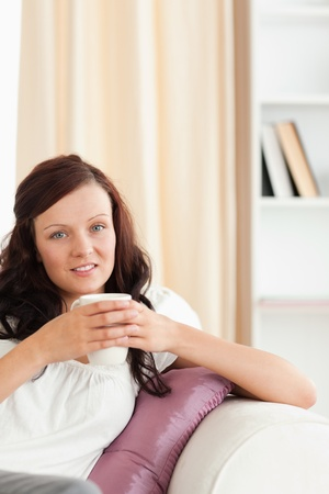 Close up of a woman holding a cup looking at the camera in her livingroom photo