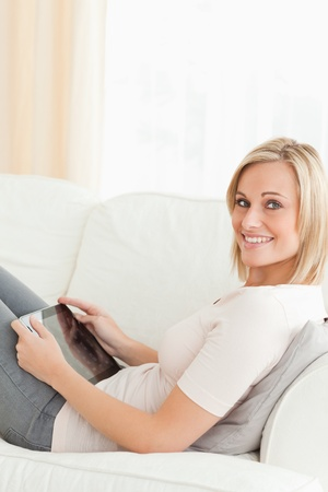 eye pad: Portrait of a woman with a tablet computer in her living room Stock Photo
