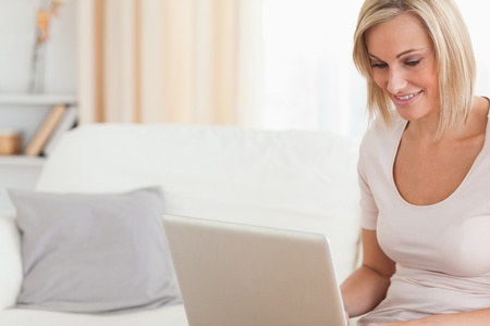 Close up of a smiling woman using a laptop in her living room photo
