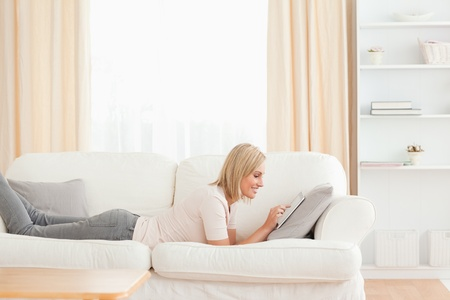 Beautiful woman using a tablet computer while lying on her sofa photo