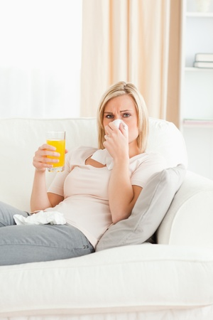 Sick blond-haired woman in her living room photo