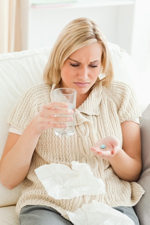 Portrait of a sick woman taking her treatment in her living room Stock Photo - 11227225