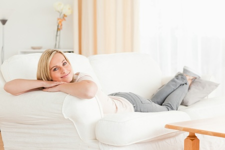 Relaxed woman lying on her sofa looking at the camera photo