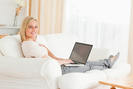 to lap: Blond-haired woman with a notebook in her living room