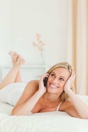 Happy woman answering the phone while lying on her bed photo