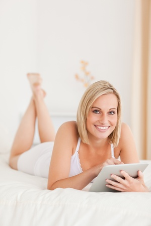 Portrait of a beautiful woman using a tablet computer in her bedroom photo