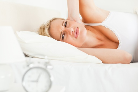 Unhappy woman awaked by her alarm clock in her bedroom photo