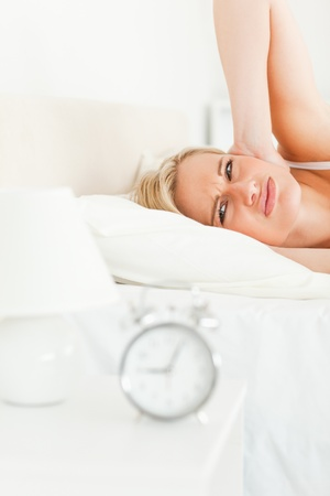 Portrait of a woman awaked by her alarm clock in her bedroom photo