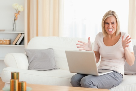 Angry blonde woman using a laptop looking at the camera Stock Photo - 11191949