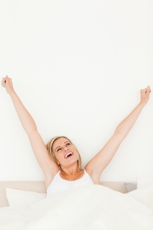 Portrait of a young woman stretching her arms in her bedroom Stock Photo - 11206529