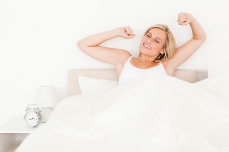Blonde woman stretching her arms in her bedroom photo