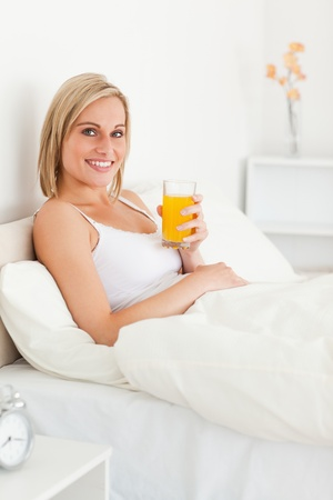 Portrait of a woman drinking orange juice in her bedroom photo