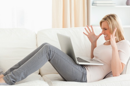 Unhappy blonde woman having trouble with her laptop in her living room photo
