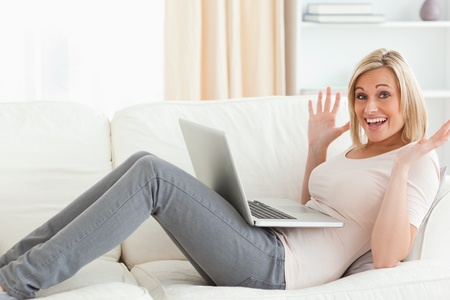 Amazed woman using her laptop in her living room photo