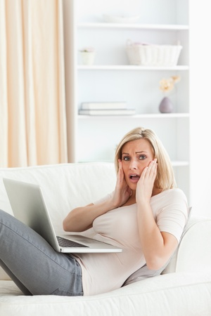 Portrait of woman having trouble her laptop in her living room photo